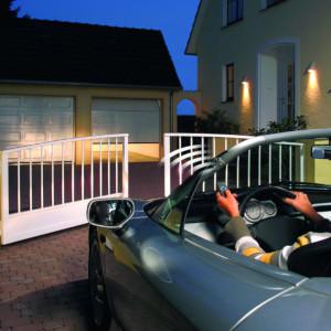 Frau öffnet Drehtor un Garagentor aus dem Auto heraus während dem Einfahren
