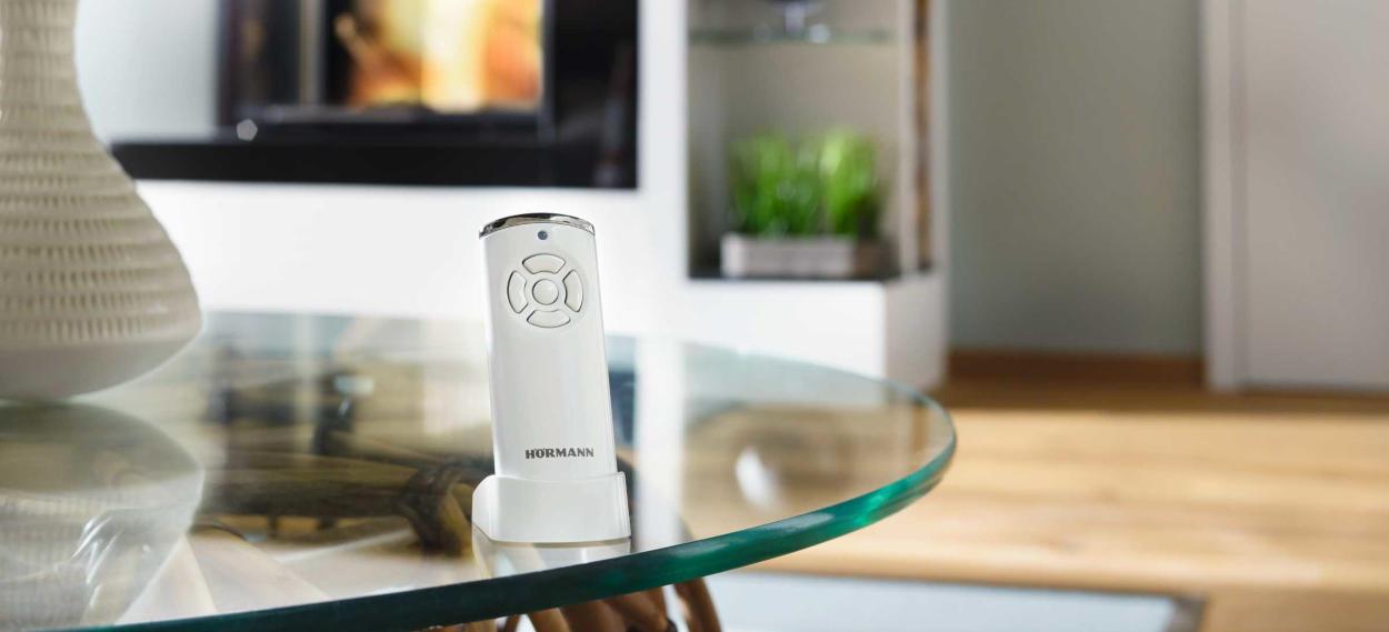 Der Hörmann Handsender 868 MHz Bisecur mit Halterung in weiß auf einem Tisch zur Inszenierung